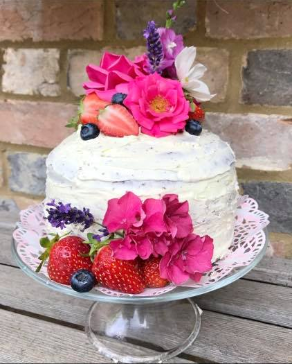 a highly decorated Victoria Sponge with flowers and strawberries