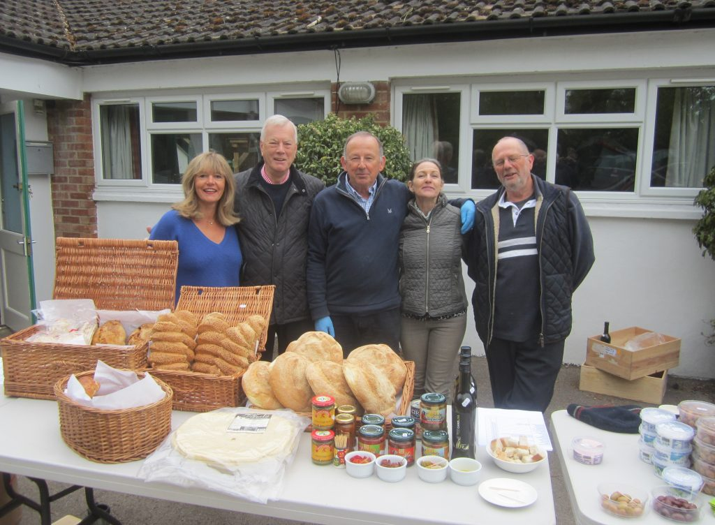 Shop volunteers (and Symeon) behind a table full of goodies at the shop's Greek monring