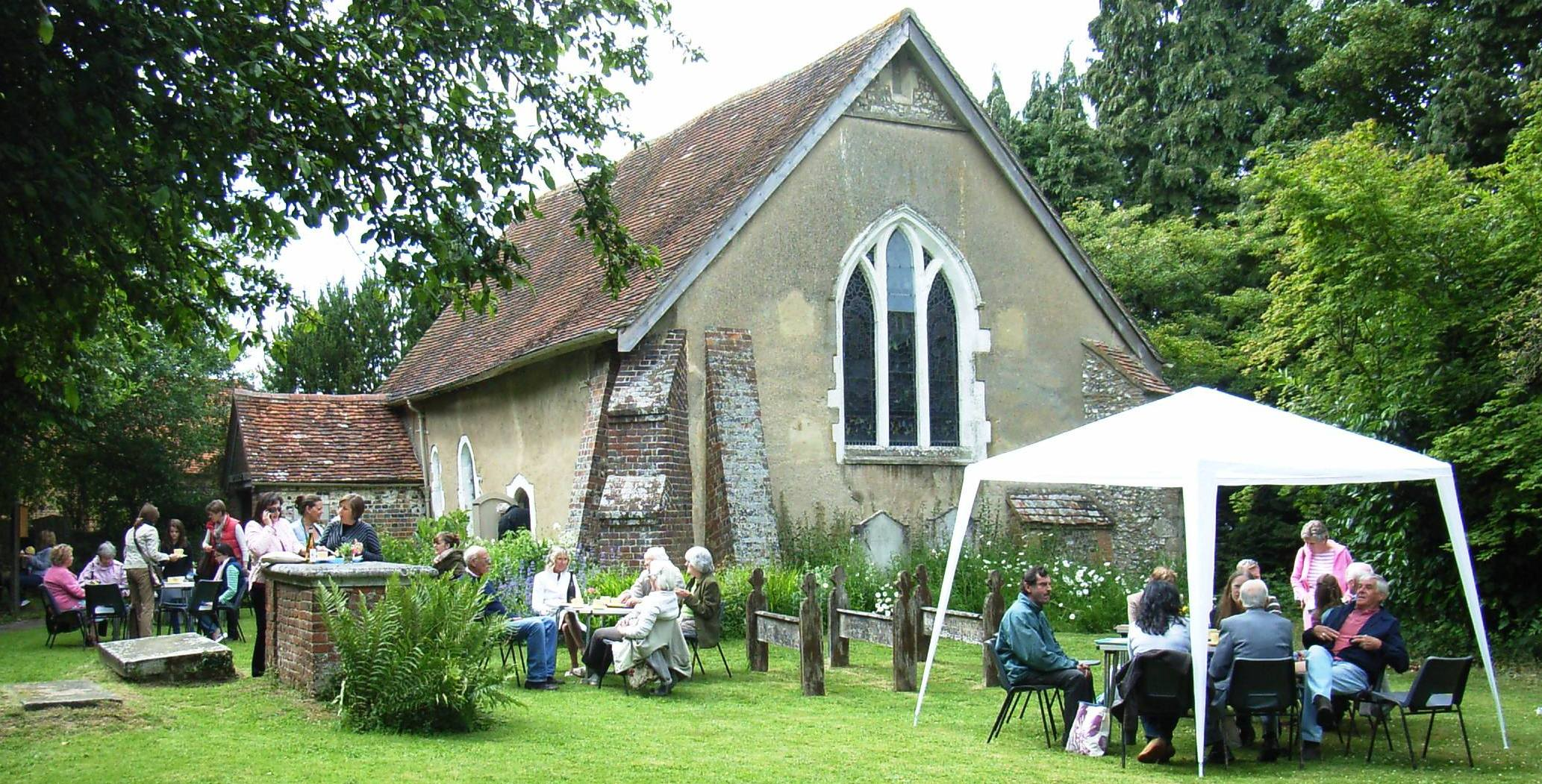 People seated outside the Old Church having cream teas