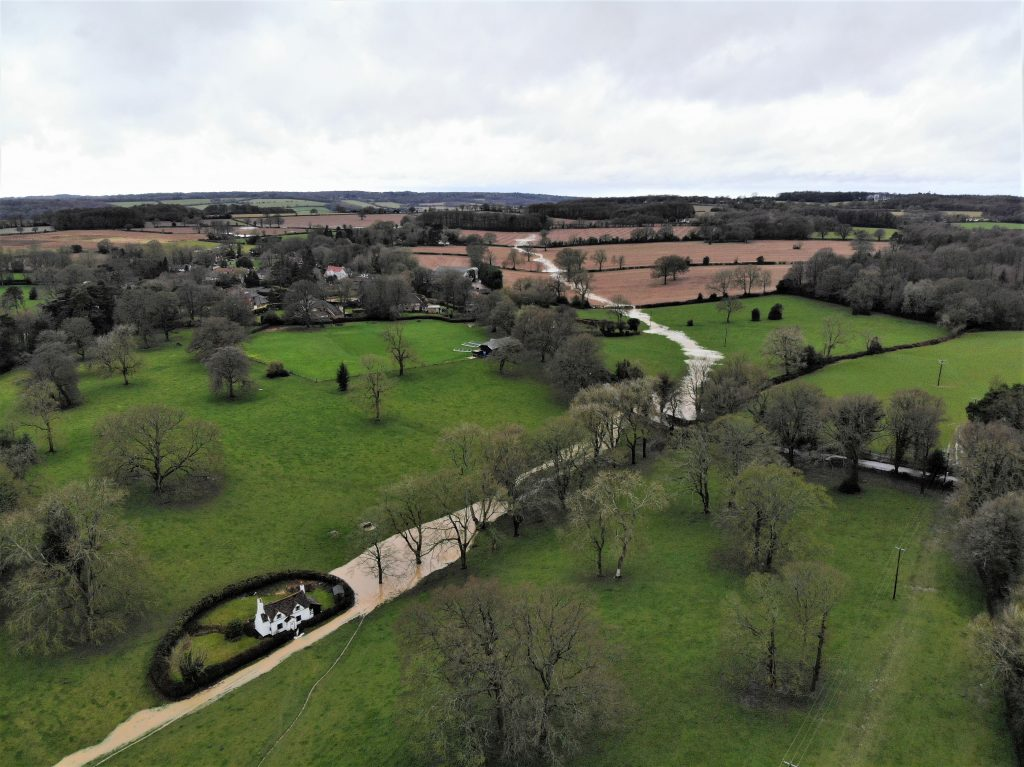 Aerial photo of Park Cottage surround by water on two sides, with a new stream created by Storm Dennis running down into the park from several fields away