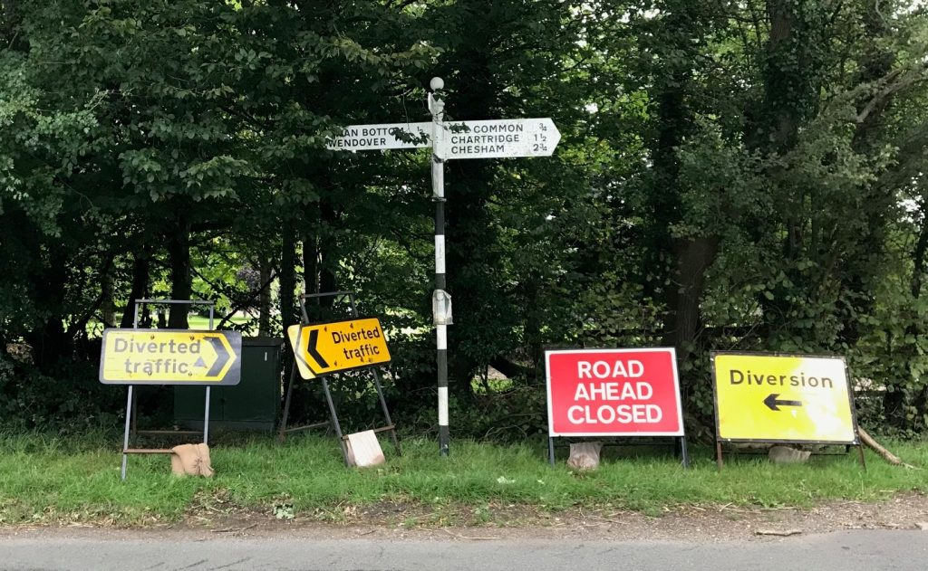 SIgnposts at the top of Lee Clump Road, pointing diverted traffic in all three possible directions