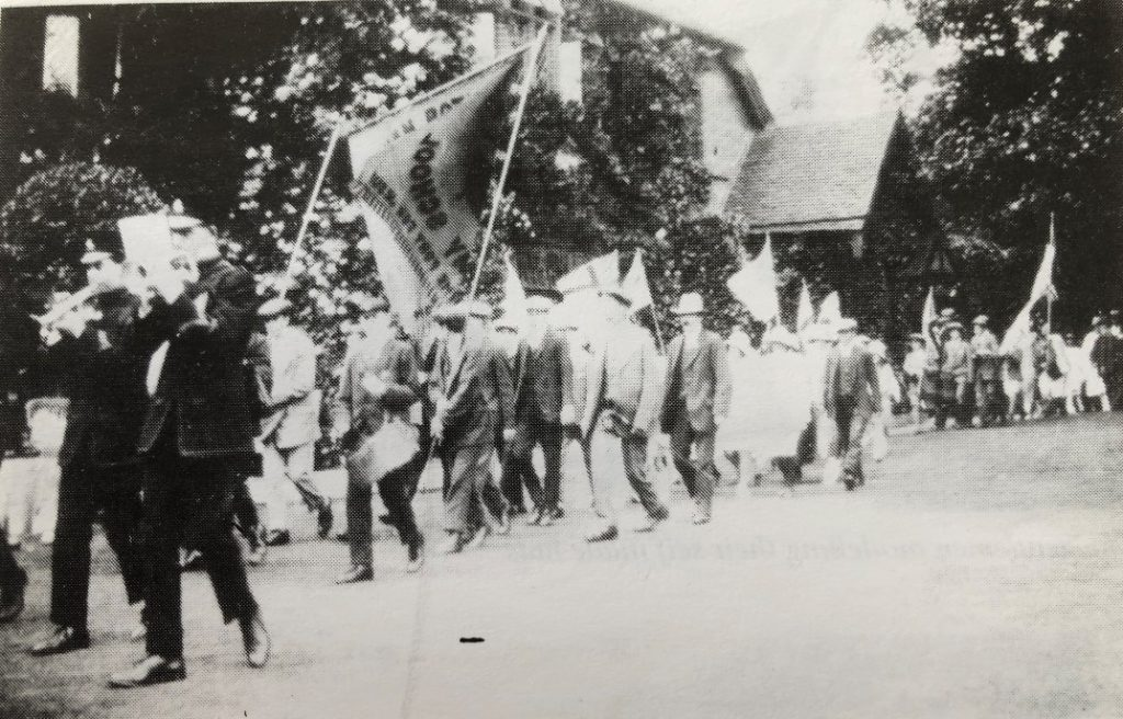 Men processing trhough the village to the church