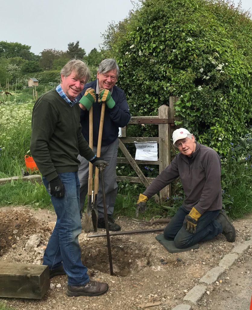 Dick, Colin and Jonathan of the TLPC Task Force looking into a large hole that they've dug ready for a new gate into the allotments.